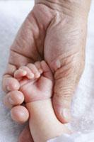 新生児の赤ちゃんと祖父の手