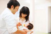 赤ちゃんにミルクを飲ませる若い夫婦