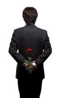 バラの花を後ろ手に持っている男性