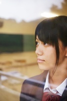 学校の教室の窓から外を見つめる女子高校生