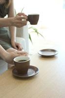コーヒーカップを持つ女性の手
