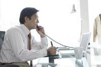 電話をしながらメモをとるビジネスマン