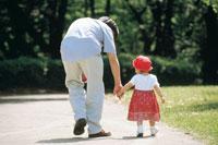 手を繋ぐ父親と子供後姿