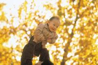 紅葉と抱え上げられる子供