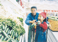 スーパーマーケットで買い物をする父親と女の子