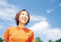青空とオレンジのTシャツを着た女性 07092000578| 写真素材・ストックフォト・画像・イラスト素材|アマナイメージズ