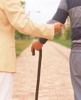 老人の腕をささえる女性の手