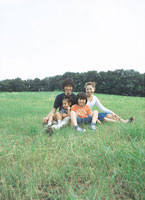 草原に座る家族4人