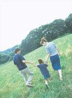 草原で手を繋ぐ家族