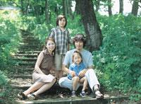 木陰の階段の前の家族4人