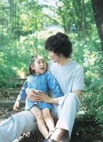 木陰で父親の膝に座る女の子