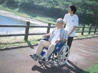 川と車椅子の老夫婦