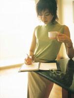 コーヒーカップを持ちメモをとる女性