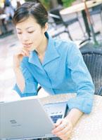 カフェでノートパソコンを開く女性