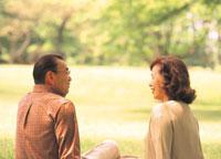 公園の芝生に座るシニアカップル