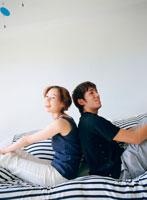 ベッドに背中を合わせて座るカップル
