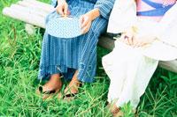 ベンチに座る浴衣のカップルの足元