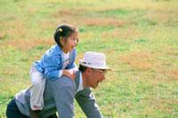 芝生で遊ぶ女の子とおじいさん