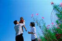 空と観覧車と子供を抱く両親