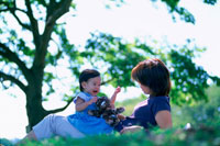 草原に寝転ぶ女の子と母親 07092002254| 写真素材・ストックフォト・画像・イラスト素材|アマナイメージズ