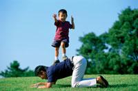 公園で父親の背中に乗る男の子