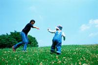草原を走る子供と母親 07092002258| 写真素材・ストックフォト・画像・イラスト素材|アマナイメージズ