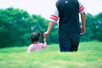 手を繋ぐ女の子と父親後姿