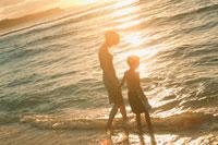 夕暮の波打ち際の母親と子供