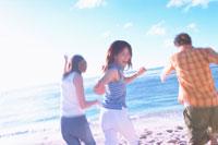 砂浜を走る若者3人