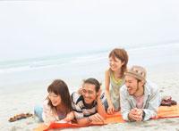 砂浜にうつ伏せになる若者4人