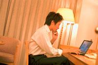 ホテルの部屋でパソコンを開くビジネスマン