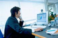 パソコンを見ながら電話をかけるビジネスマン