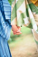 手を繋ぐ浴衣のカップル
