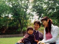 公園の芝生に座る家族3人