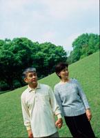 公園を手を繋いで歩くシニアカップル