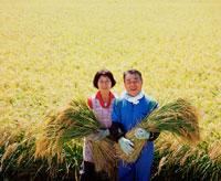 稲穂を持つ夫婦