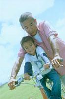 公園で自転車に乗る父親と女の子
