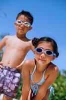 青空とサングラスを首にかけた水着の子供2人