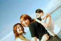 浜辺で肩を組む女性3人