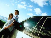 砂浜に止めた車の前に立つカップル