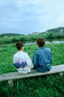 草原のベンチに座る浴衣のカップル後姿