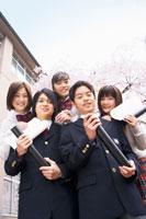 校舎前で丸筒を持って集まる学生達
