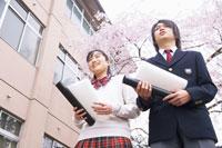 校舎前で丸筒を持つ学生達