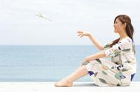 海辺で飛行機を飛ばす女性