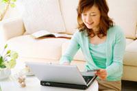 ソファの前に座ってパソコンするミドル女性