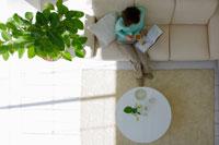 ソファに座って本を読むミドル女性