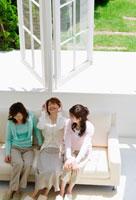 ソファに座って話すミドル女性3人