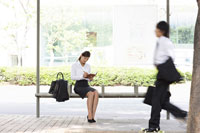 バスを待つスーツの女性と歩く男性