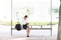 バスを待つスーツの女性