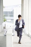 携帯電話で話しながら走るビジネスマン 07135002235| 写真素材・ストックフォト・画像・イラスト素材|アマナイメージズ